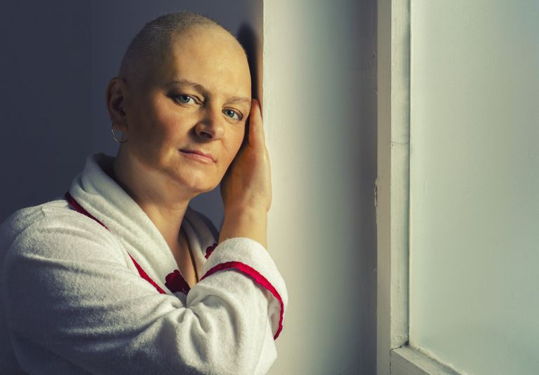 bald woman on chemotherapy leaning against door
