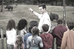Zoo keeper with group of children at rhino exhibit