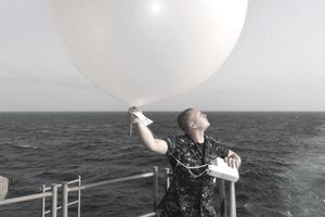 U.S. Navy Aerographer's Mate 3rd Class Robert Dietrich launches a weather balloon off the fantail of the aircraft carrier USS Harry S. Truman (CVN 75) June 28, 2010, while under way in the U.S. Fifth Fleet area of responsibility.