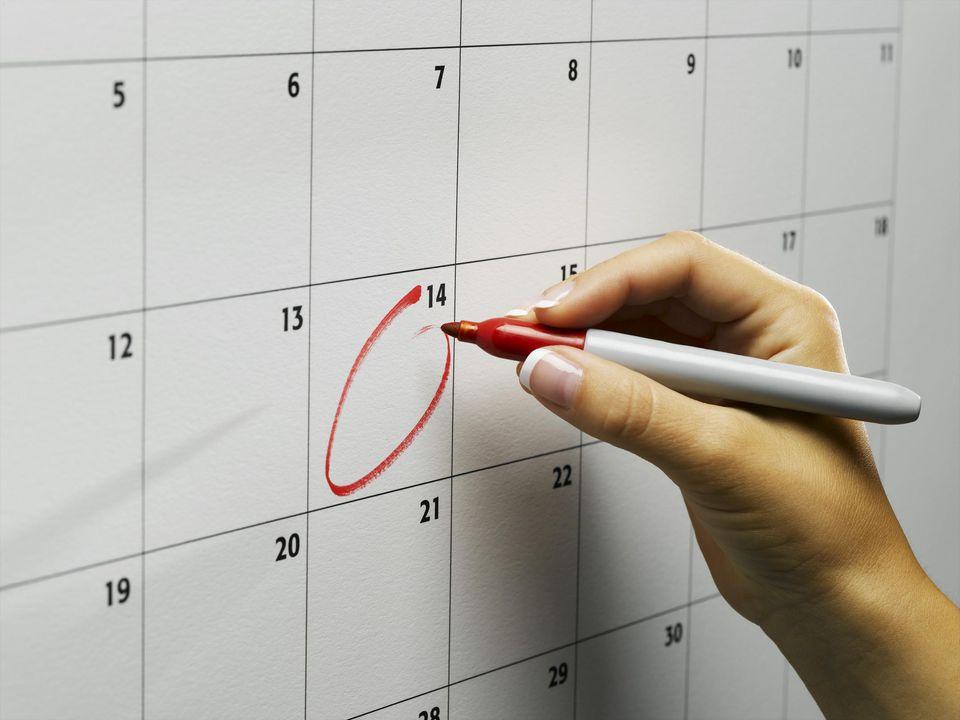 Woman circling day on wall calendar, close-up
