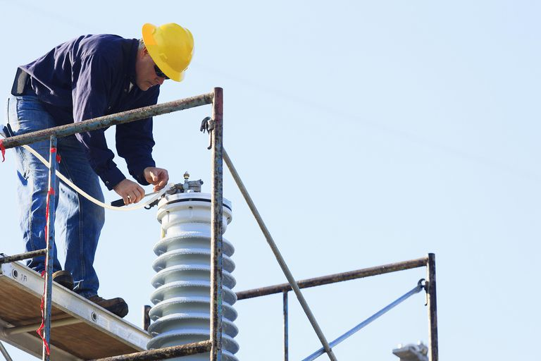 Engineer working on high voltage insulator.