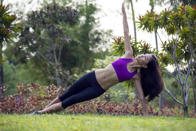Young woman is exercising and meditating in the gardens, Singapore.