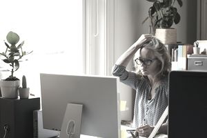 Stressed woman with hand in hair holding credit card at computer in home office