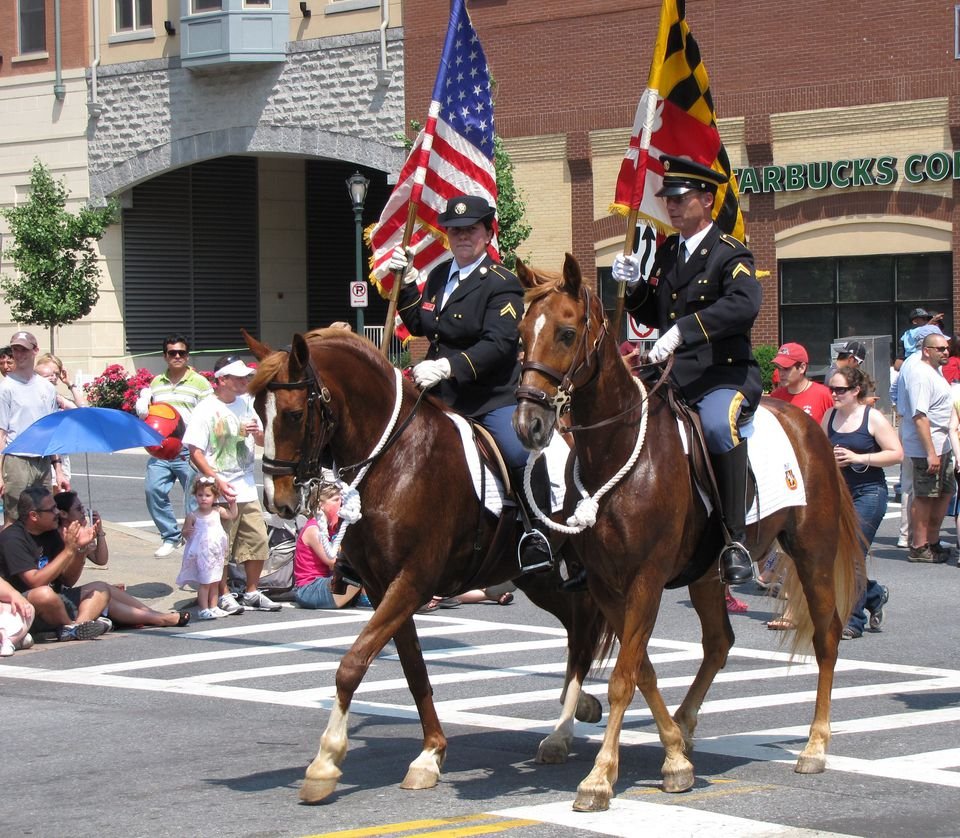 Two men carrying the US and Maryland flags riding horses in a parade