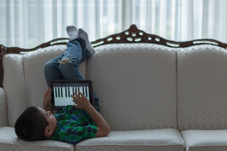 Boy playing piano on tablet computer
