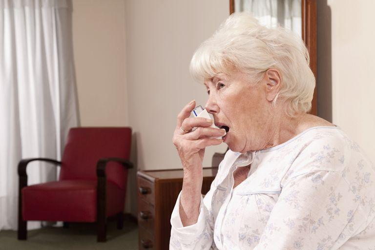 Close-up of a woman using inhaler