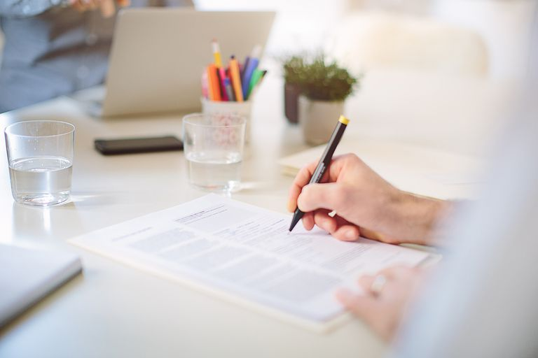 man signing document at desk