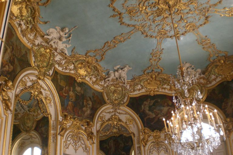 Highly decorative walls and ceiling in an oval chamber, looking up toward an ornate chandelier