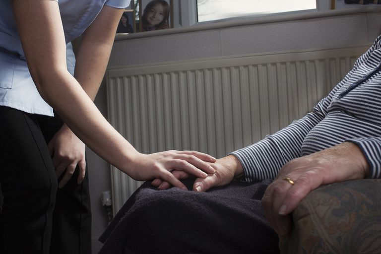 Personal care assistant comforting senior woman