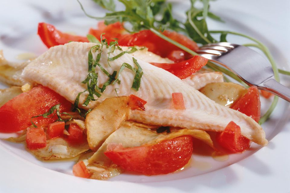 Salad with steamed tomato and fish on plate, close-up