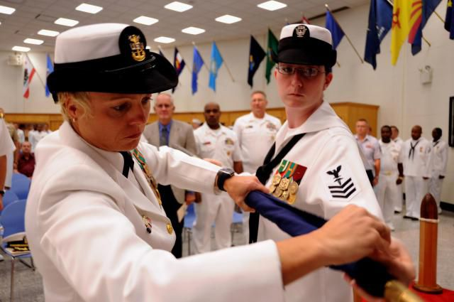 Sailors furl the colors of the Naval Hospital Corps School Great Lakes during a disestablishment ceremony