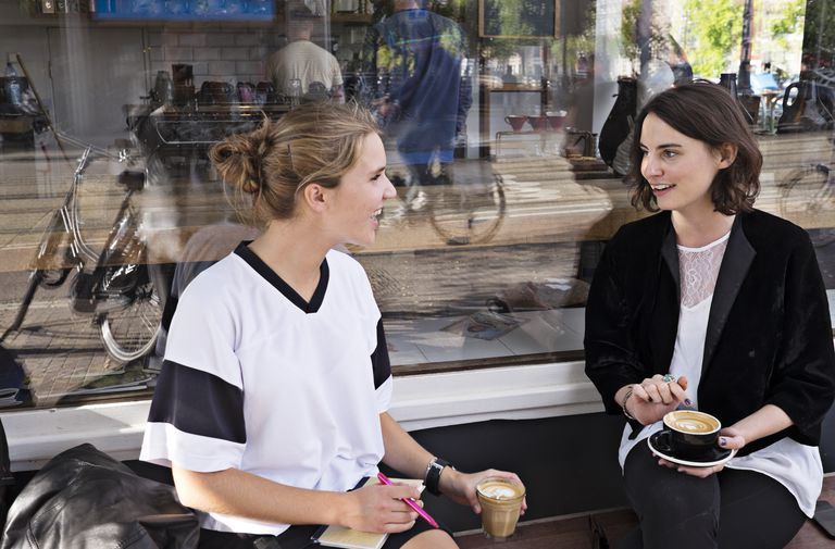 Two women chat outside cafe