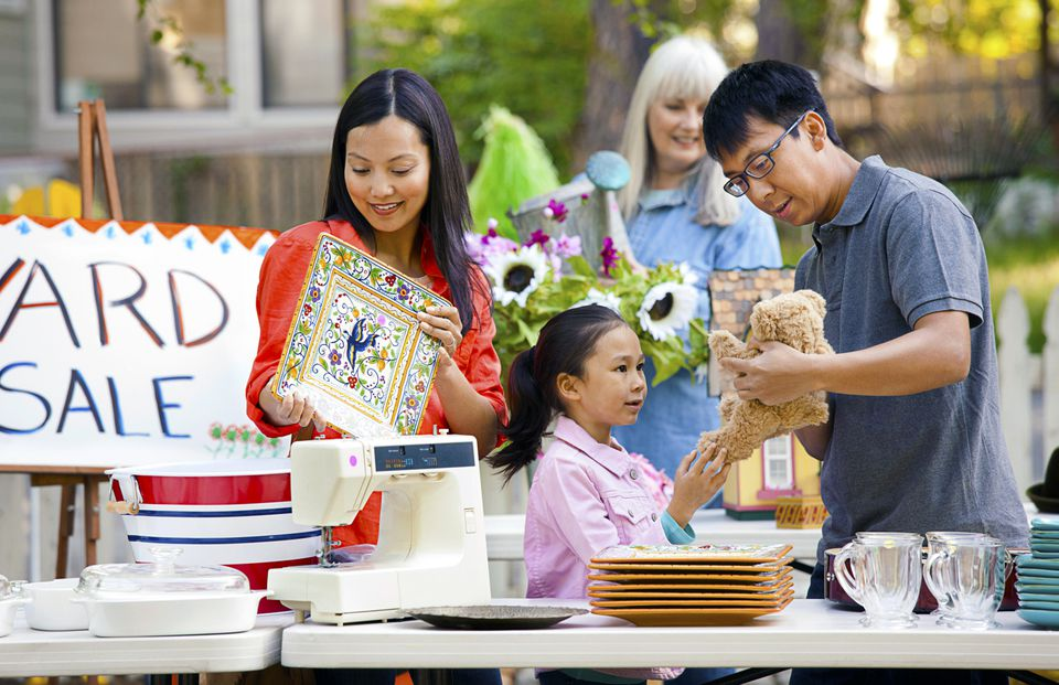 Asian family at a yard sale looking at stuff for sale