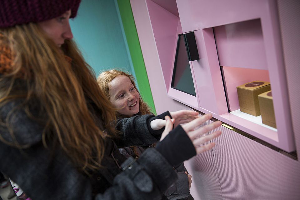 Lucie Mason, age 9 (C), and her babysitter, Laura Flanagan, receive their order of cupcakes from a 'Cupcake ATM' created by Sprinkles bakery on March 25, 2014 in New York City. The Cupcake ATM opened today, and while there were certain technical difficulties for the first day, lines of people waited to try out the new machine.