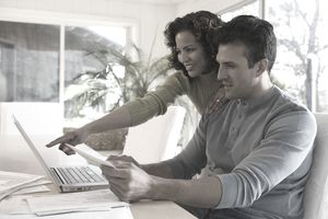 Couple looking at bills and laptop