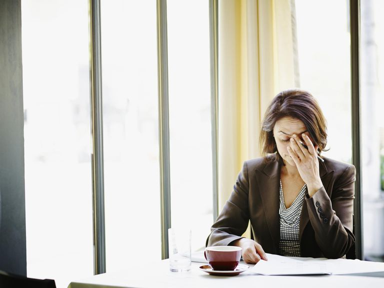 Businesswoman at table with head resting o...