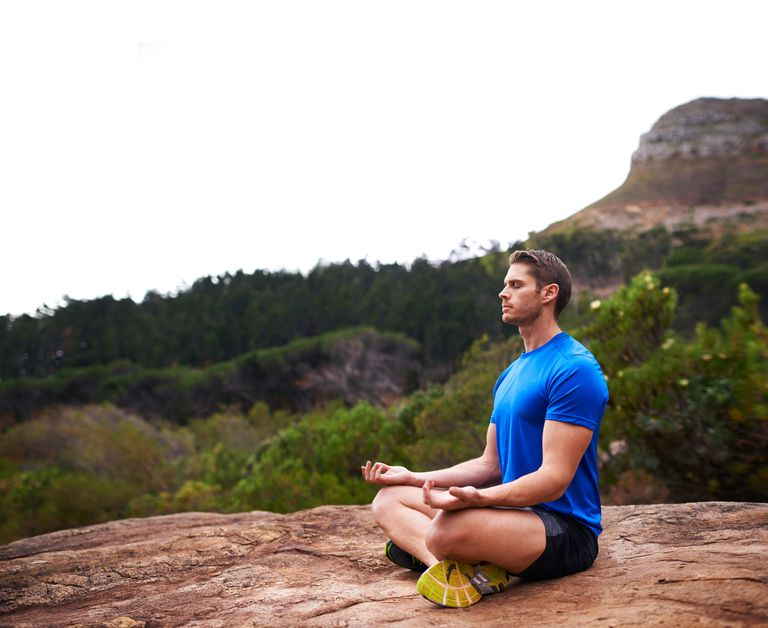man in running clothes meditating outside on a boulder