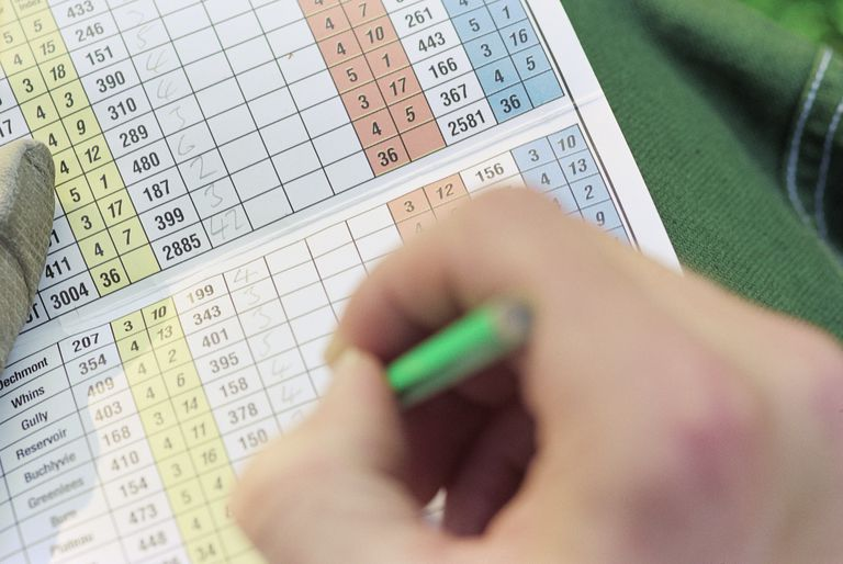 A golfer pencils in his scores on a golf scorecard