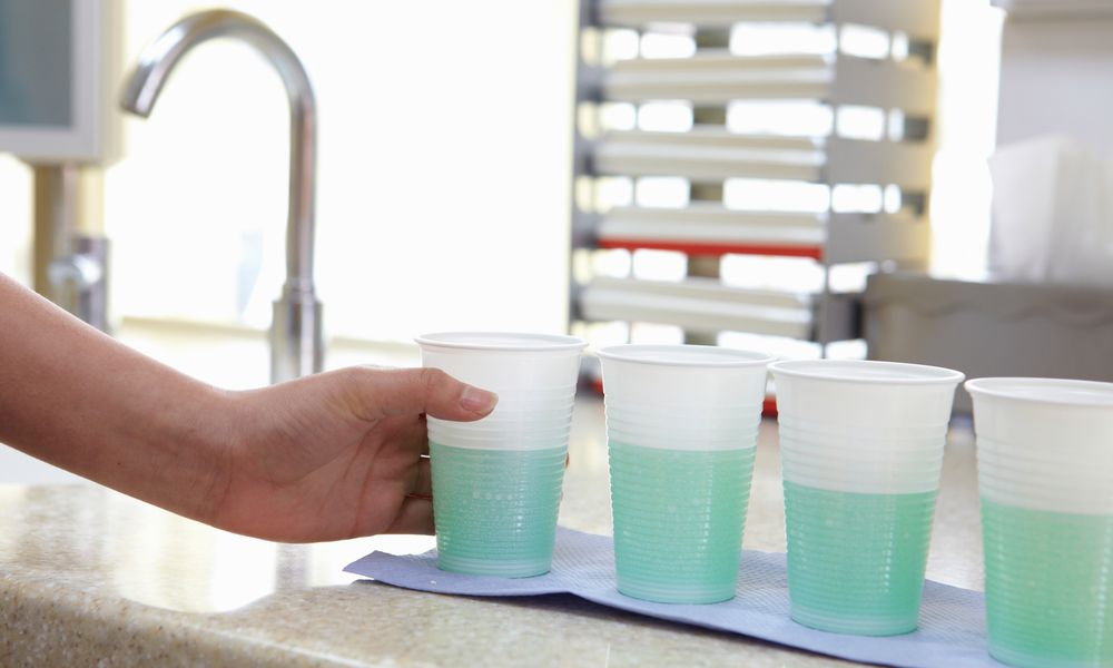 Dental assistant preparing cups of mouth rinse