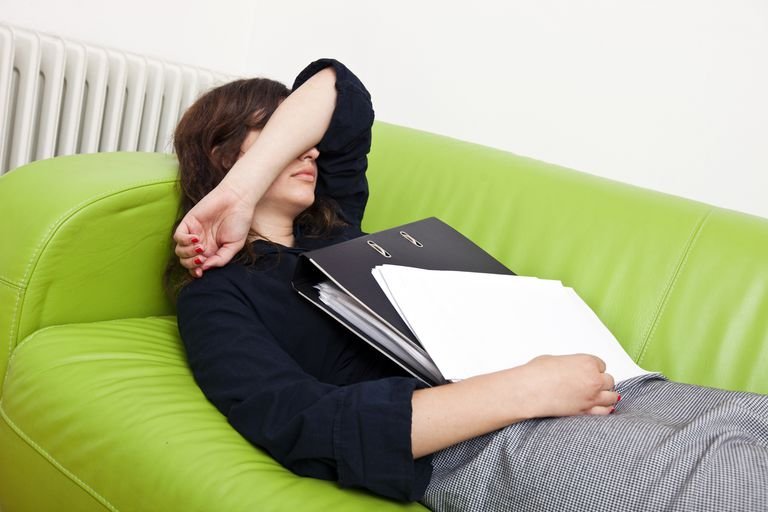A woman lies on the couch with her arm over he face.