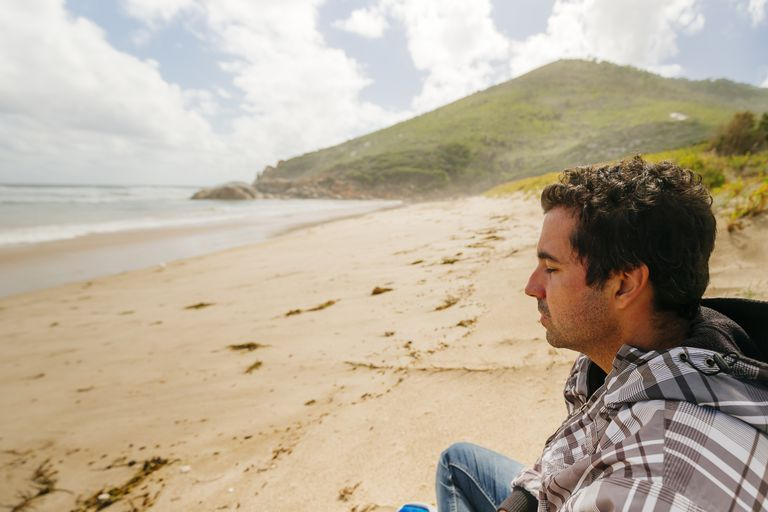 Profile of a man seating on an empty beach with eyes closed, in Wilson Promontory