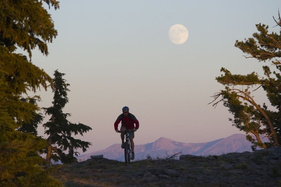 A man bikes beneath the full moon above Lake Tahoe in California.