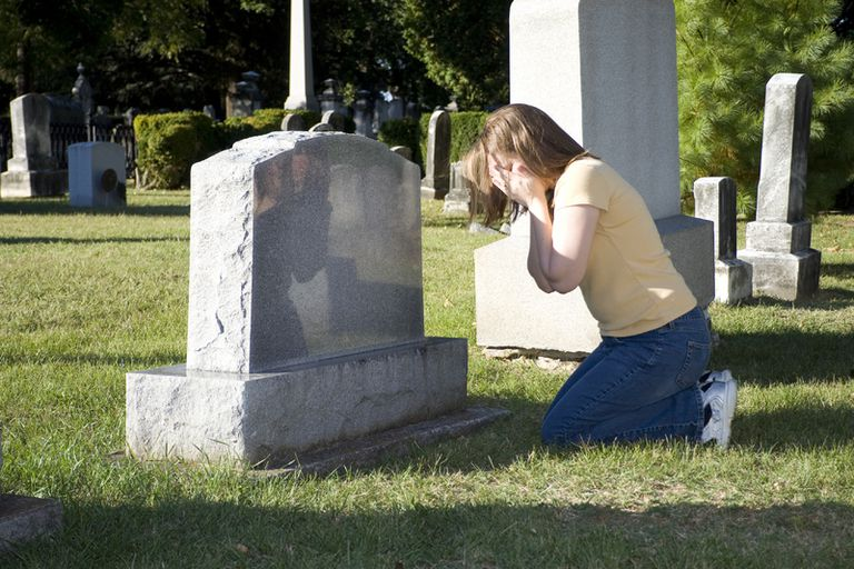 Woman kneeling at gravestone