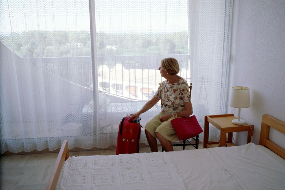 Senior woman with luggage sitting by window in hotel room