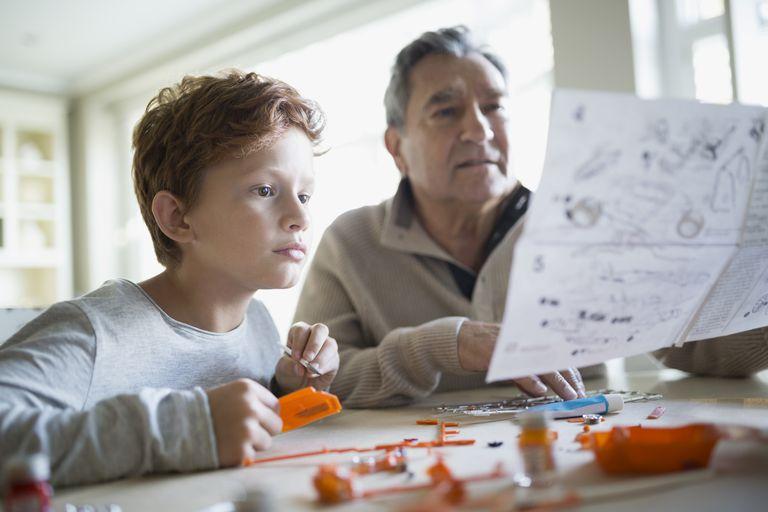 man and boy assembling a model