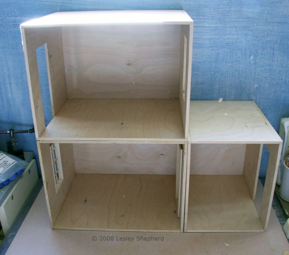 A group of different sized roomboxes laid out to make a simple dolls house.