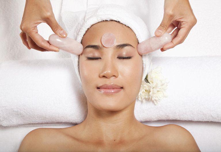 Woman receiving facial massage with rose quartz