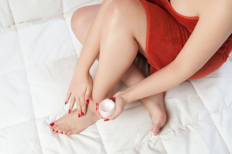 Woman wearing red towel applies lotion to her feet