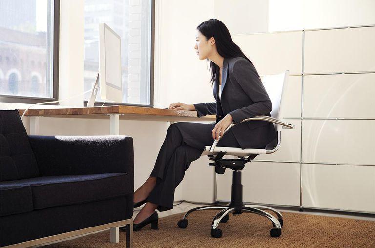 Woman sitting at desk facing window
