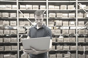 man in a warehouse holding a tablet
