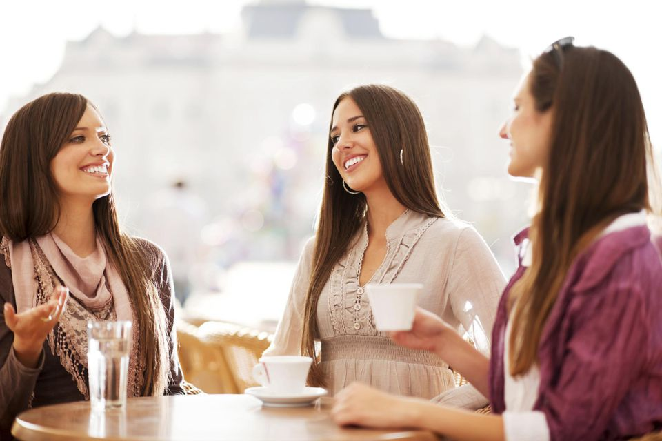 Three young women drinking coffee in a cafe