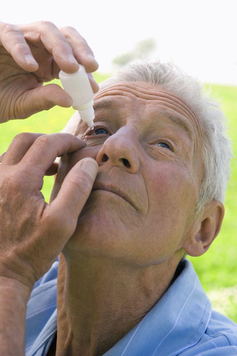Older man using eye drops