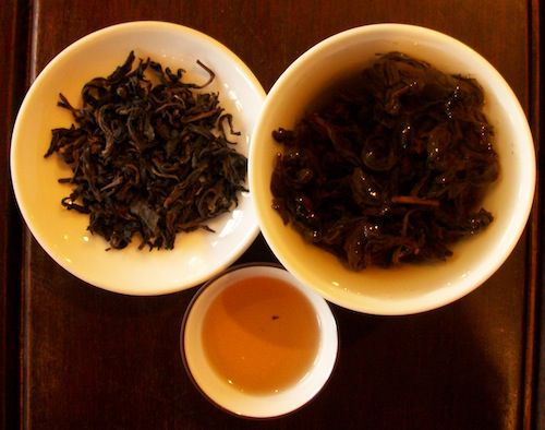 An image of an Aged Baozhong Taiwanese Oolong tealeaves, brewed tea and brewed tealeaves.