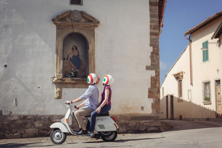 Couple looking at church painting from moped in Florence, Italy