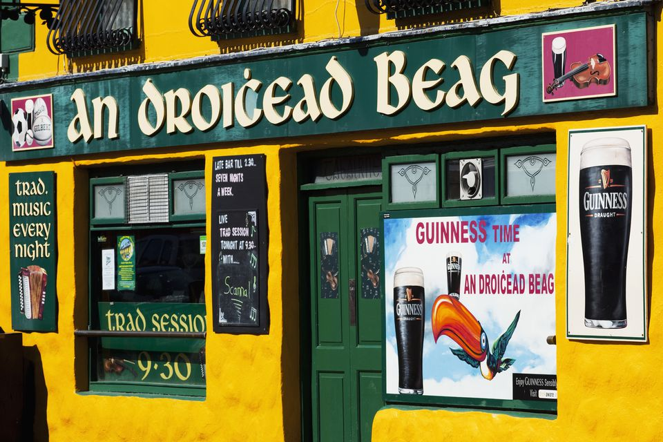 A bar with green and yellow facade and signs advertising beer; Dingle Town, County Kerry, Ireland