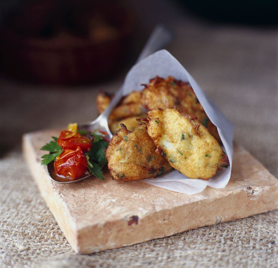 Croquetas de bacalao (Salt cod croquettes) in a paper cone with a spoon full of tomato salsa, on a tile, close-up