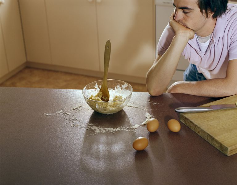 Young man looking at mixing bowl on kitchen counter, elevated view