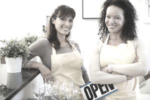2 women in aprons with an Open sign