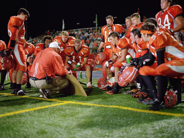 American football players including teenagers (15-17) and coach planning tactics