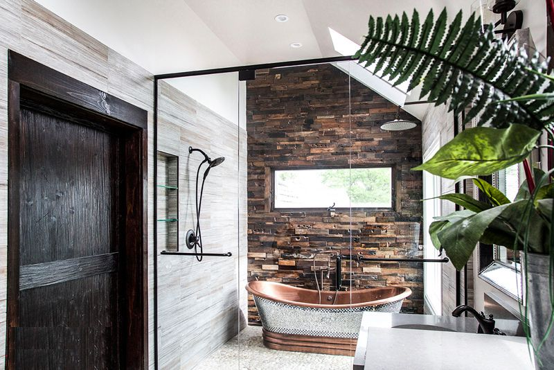 A luxury bathroom with a rustic, metallic bathtub
