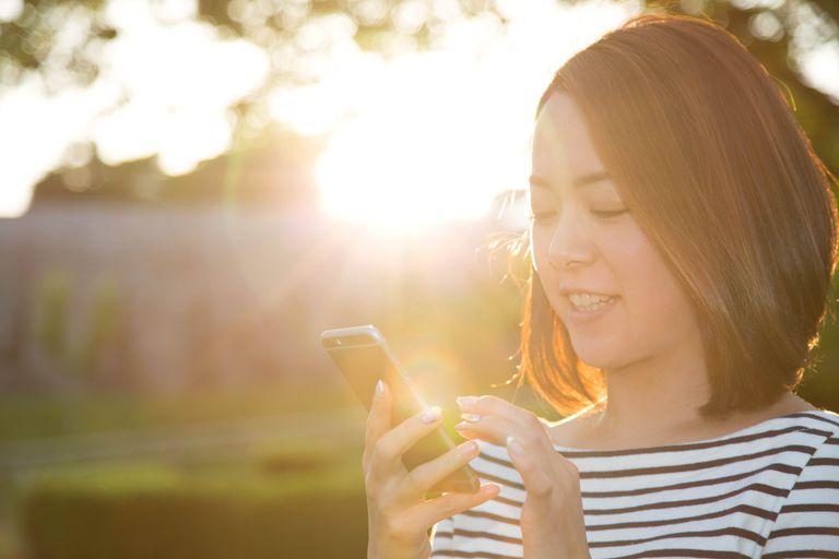 Woman using an ovulation calculator/calendar app on her smart phone