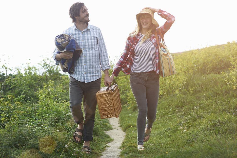 Couple walking and laughing on coastal path with picnic hamper.
