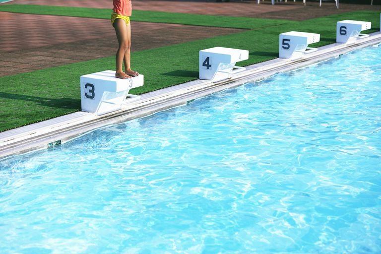 Little girl standing on springboard beside pool
