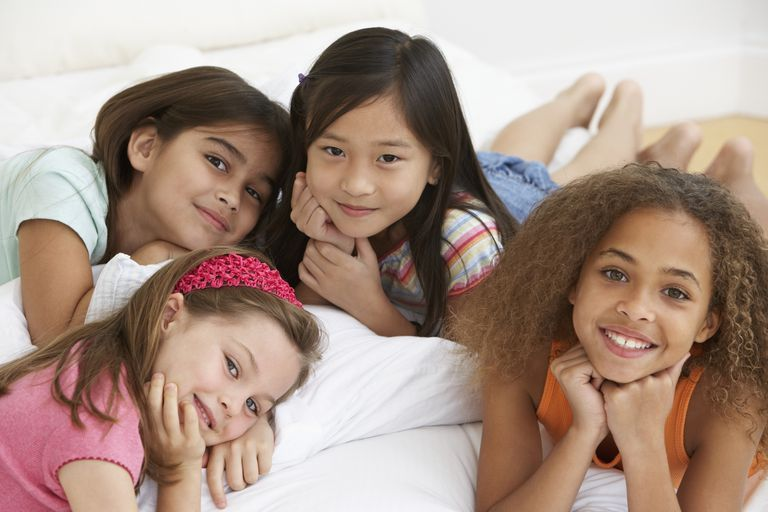 9 year old child - girls smiling on bed