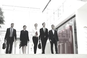 five business professionals walking in office building