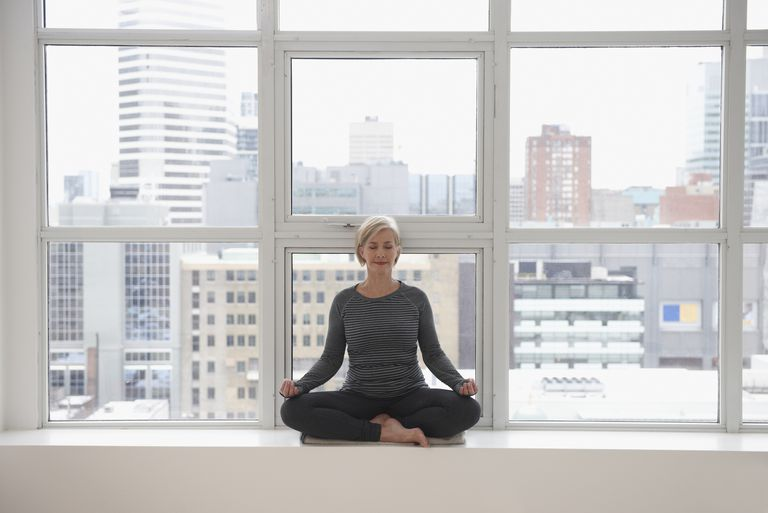 Mature woman meditating in front of a window with a city in the background